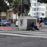 Foto de um idoso em situação de rua sentado aos pés da estátua em homenagem aos 18 do forte