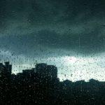 Silueta de edifícios atrás de uma vidro chapiscado de chuva